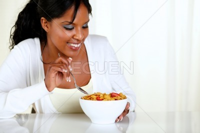 Afro-american female eating a bowl of cereals