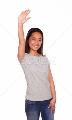 Asiatic young woman greeting with her hand up