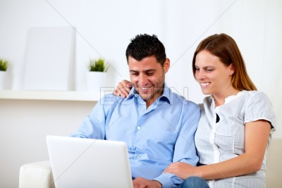 Attractive couple smiling and looking to computer