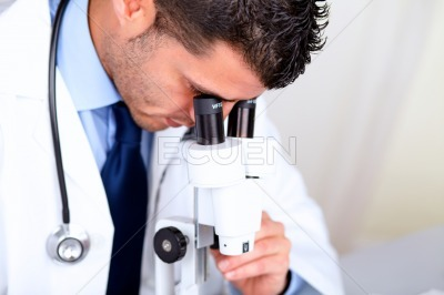 Attractive latin doctor using a microscope