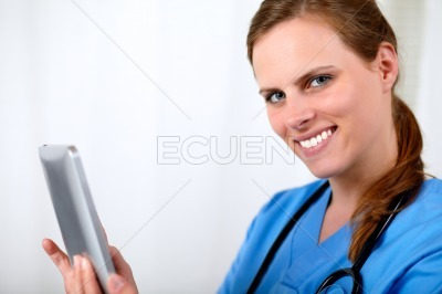 Beautiful blonde nurse smiling with a tablet PC