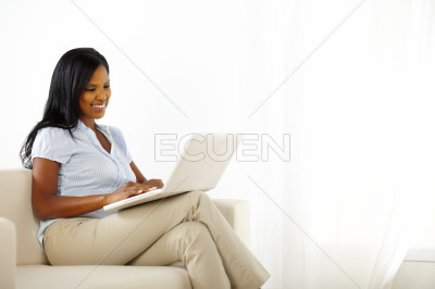 Beautiful friendly young woman working on laptop