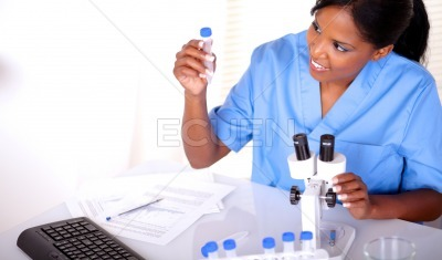 Beautiful scientific woman looking to test tube
