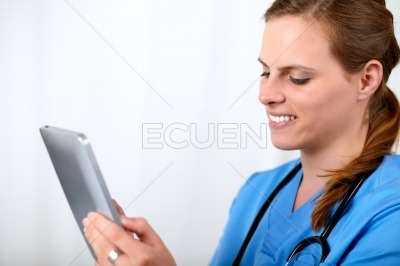 Beautiful surgeon woman smiling with a tablet PC