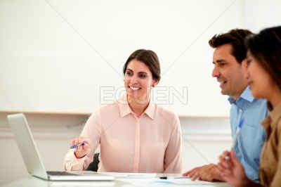 Beautiful woman explaining ideas to her coworkers