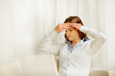 Beautiful woman with headache in from laptop