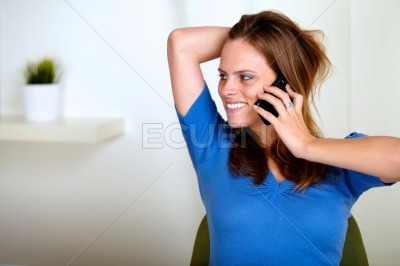 Blonde friendly young woman conversing on phone