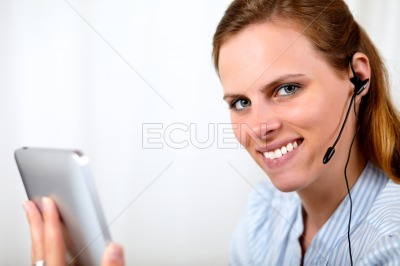 Blonde girl talking and holding tablet PC