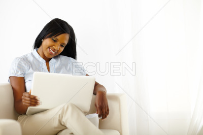 Calm young woman working on laptop