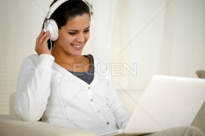 Charming female with headphone listening music