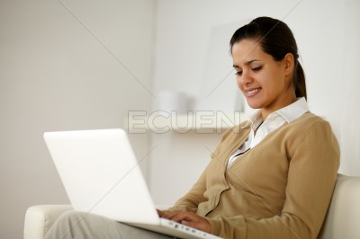 Charming latin young female using her laptop