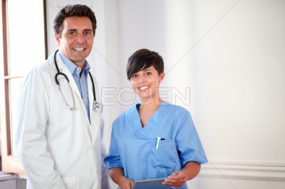 Charming male doctor and pretty nurse standing