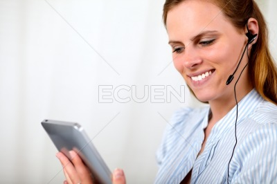 Charming pretty girl looking to a tablet PC
