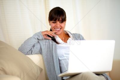 Charming woman sitting on sofa in front of laptop
