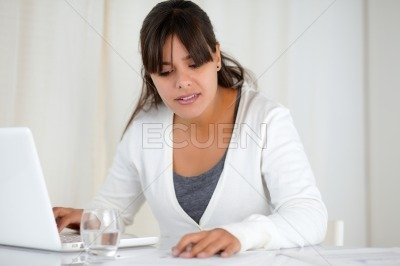 Charming woman working at office with a laptop