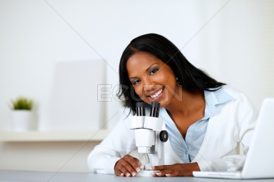 Charming young female using a microscope