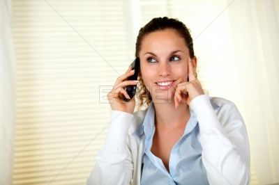 Charming young woman listening on cellphone