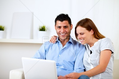 Couple having fun on laptop at home