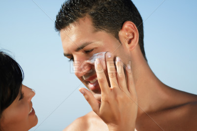 Couple on the beach putting on cream