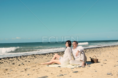 Couple sit down on the beach