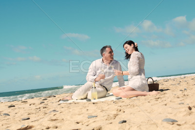 Couples picnicking on the beach