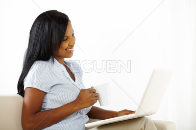 Cute young woman working on laptop at home