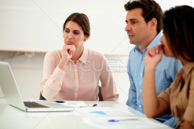 Ethnic coworkers looking at a laptop