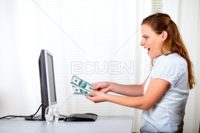 Excited blonde girl holding plenty of cash money