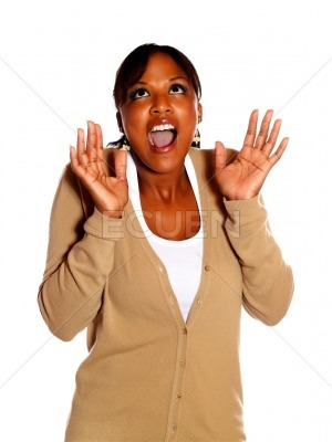 Excited young woman screaming with hands up