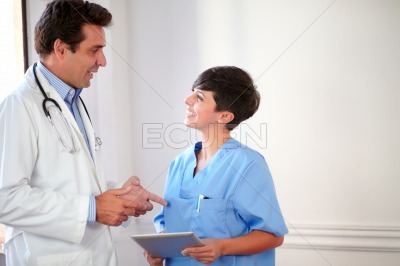 Female nurse listen to male hispanic doctor