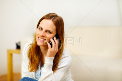 Friendly girl speaking on the phone at home