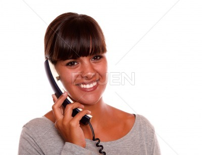 Friendly young woman speaking on phone