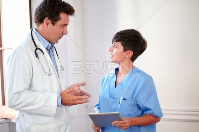 Handsome doctor talking to pretty nurse