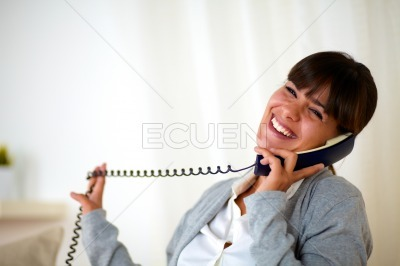 Happy laughing woman conversing on phone at home