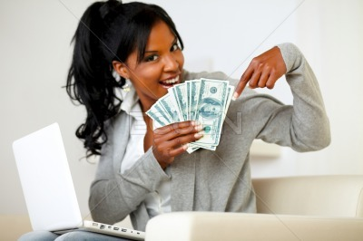 Happy young woman pointing plenty of cash money