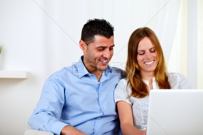 Lovely couple smiling and using a laptop