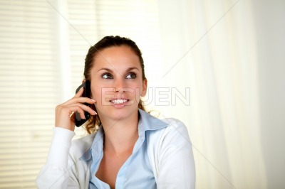 Lovely young woman conversing on cellphone