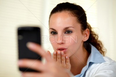 Lovely young woman kissing to cellphone