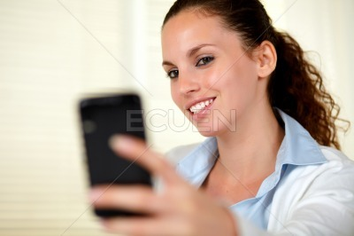 Lovely young woman sending a message with mobile