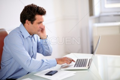 Male hispanic boss working on his laptop