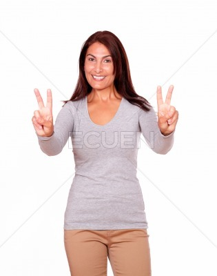 Mature woman gesturing victory sign with fingers