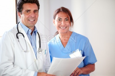 Medical couple smiling and looking at you