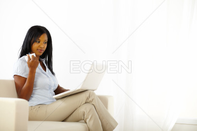 Mistrusted young woman working on laptop