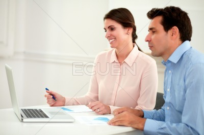 Office guy and lady looking at laptop