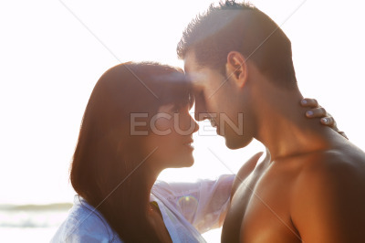 Passionate couple in love kissing and embracing between backli