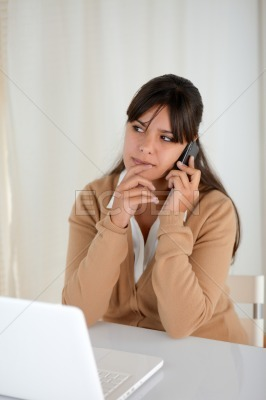 Pensive woman working and speaking on cellphone