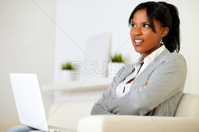 Pensive young woman sitting on sofa with a laptop