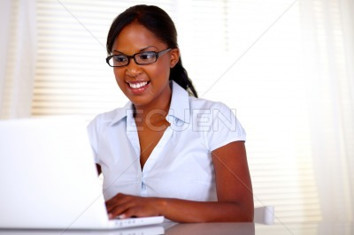 Pretty female with black glasses working on laptop