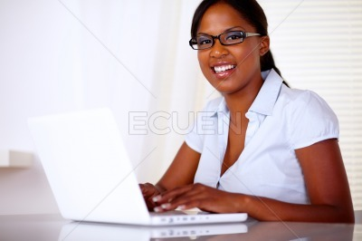 Pretty woman looking at you working on laptop