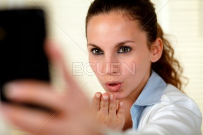 Pretty young woman kissing to cellphone